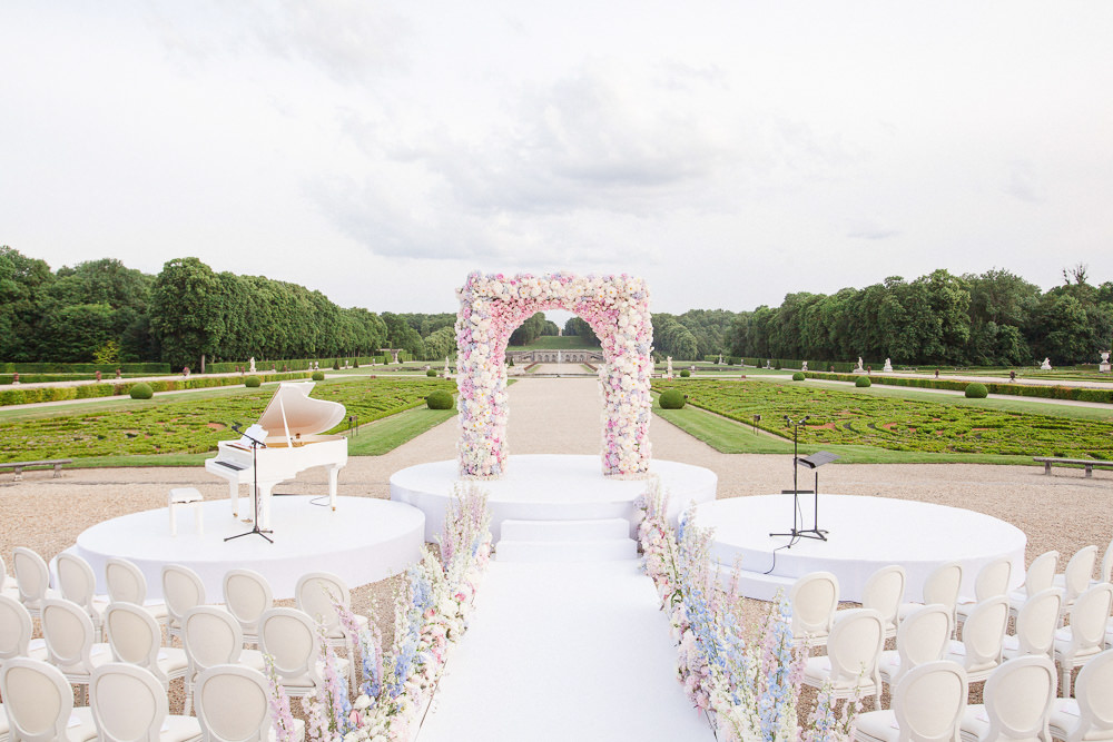 Wedding ceremony setup with pink and while flowers at Vaux le Vicomte French chateau