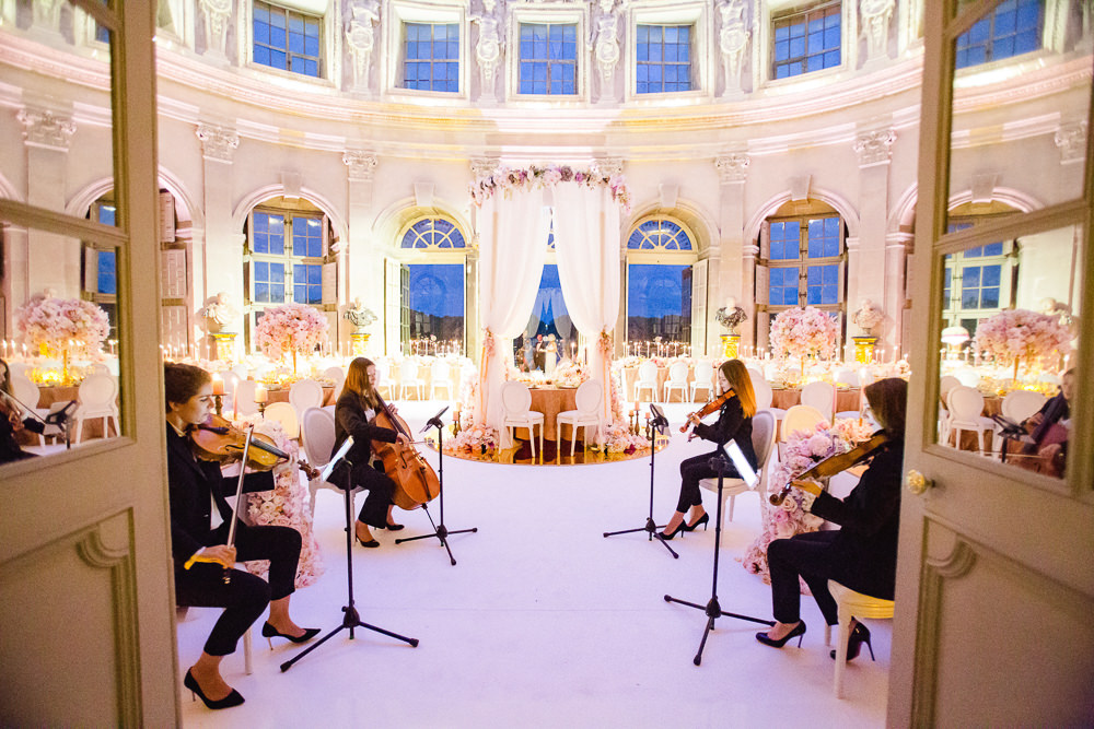 Vaux le Vicomte wedding reception setup - Classical musicians playing, room filled with candles and flowers