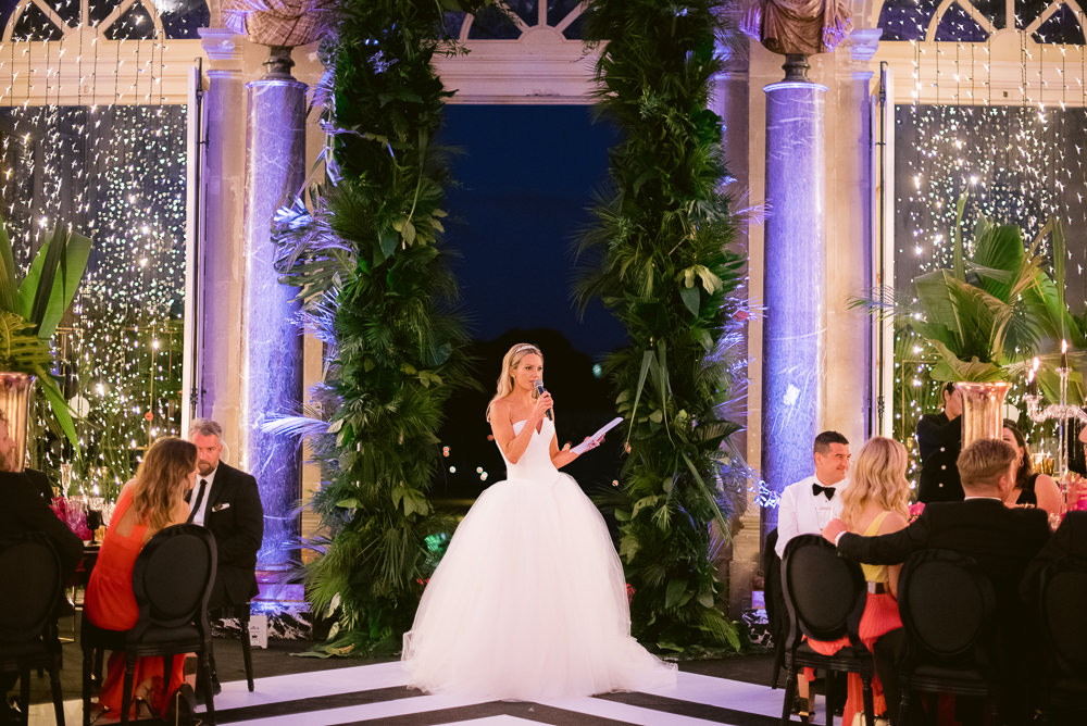 Modern bride having speech during Vaux le Vicomte wedding dinner in a French chateau near Paris