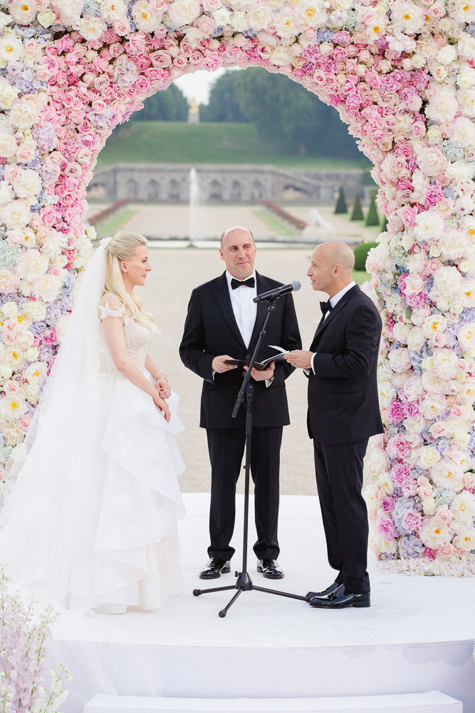 Bride and groom exchanging vows during wedding ceremony in the gardens of a French chateau near Paris